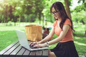 mulher asiática usando e digitando no teclado do laptop no parque ao ar livre foto