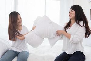 duas garotas asiáticas fazendo guerra de travesseiros no quarto durante a infância foto