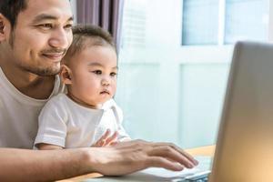 pai solteiro e filho usando laptop juntos e felizes foto