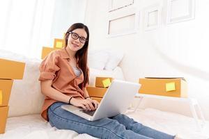 Mulher asiática bonita usando laptop para atendimento ao cliente no quarto foto
