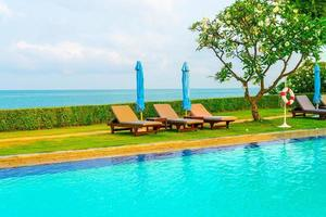 cadeira de piscina e guarda-sol ao redor da piscina foto
