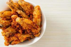 Asas de frango de churrasco frito na tigela foto