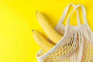 bananas maduras em saco de malha em fundo amarelo. sacola de compras ecológica. foto