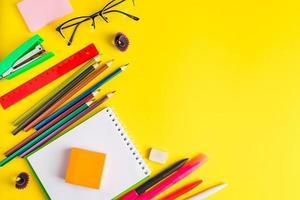 postura plana de artigos de papelaria em fundo amarelo. de volta à escola foto