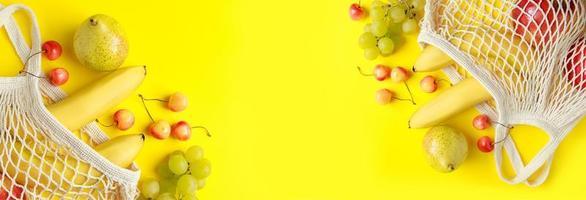 frutas maduras em saco de malha em fundo amarelo. foto