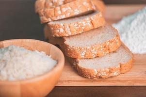 fatia pão de arroz e farinha em uma tábua de madeira foto