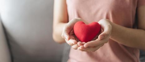 mulher segura coração vermelho, amor, seguro saúde, doação, caridade feliz foto