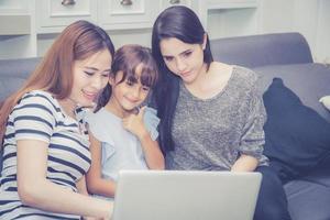 família e filha, tendo tempo para aprender com o computador portátil. foto