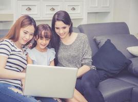 família e filha, tendo tempo juntos aprendendo com o uso do laptop. foto
