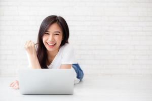 jovem mulher asiática, animada e feliz com o sucesso com o computador portátil. foto