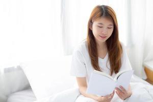 jovem mulher asiática relaxar sentado lendo um livro no quarto. foto