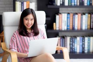 jovem mulher asiática trabalhando no computador portátil. foto