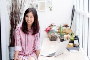 jovem mulher asiática trabalhando no laptop sentado na cafeteria. foto