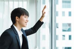 um homem em um terno de negócio olha pela janela foto