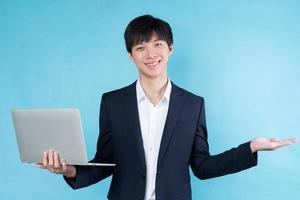 imagem de jovem empresário asiático vestindo um terno em um fundo azul foto