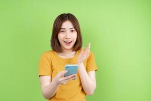 jovem asiática posando sobre fundo verde foto