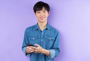 retrato de homem asiático de camisa azul, posando em fundo roxo foto