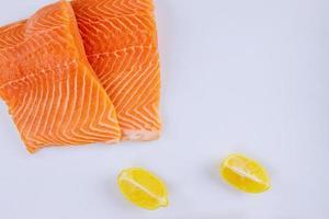 dois filés de salmão cru com limão no fundo branco foto