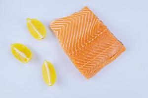 filé de salmão fresco com limão no fundo branco. foto