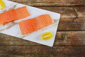 Peixe delicioso filé de salmão cru com rodelas de limão no tabuleiro de mármore foto