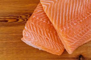 Filé de salmão cru fresco na tábua de madeira foto