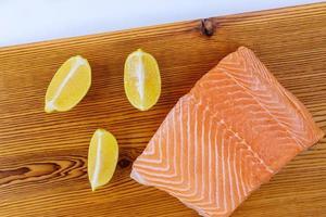 filé de salmão cru fresco com tábua de madeira foto