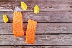 delicioso peixe filé de salmão cru com rodelas de limão na tábua de madeira foto