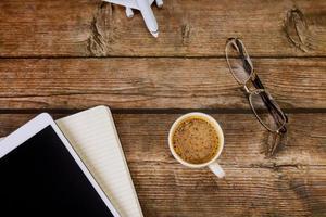 vista superior da mesa do escritório com bloco de notas digital para tablet, café expresso foto