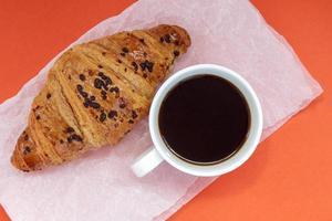 café preto sem leite em uma xícara branca e um croissant de chocolate foto