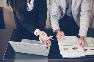 empresária e empresário analisando documentos foto