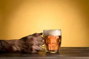 homem segurando copo de cerveja na mesa de madeira foto