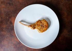 costeleta de porco assada, lombo de porco grelhado servido em prato branco foto