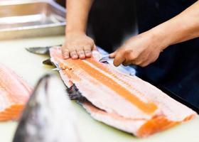 chef usando uma faca para cortar filé de salmão em restaurante foto