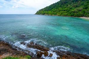 litoral rochoso sob céu azul claro foto