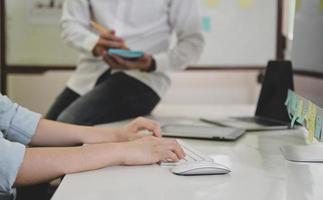 mãos trabalhando no teclado do computador e pessoas sentadas na mesa. foto