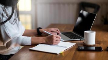jovem trabalha em casa, ela usa um laptop e faz anotações. foto