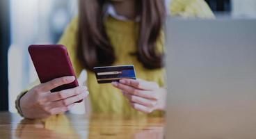jovem pagando online por smartphone e cartão de crédito. foto