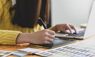 designer feminina desenhando em um tablet gráfico digital. foto