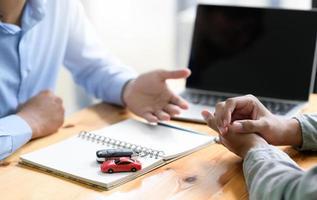 o corretor de seguros está recomendando seguro contra acidentes de automóveis aos clientes. foto