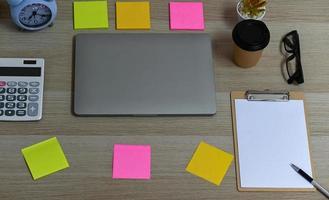 laptop com prancheta em branco e calculadora com material de escritório. foto