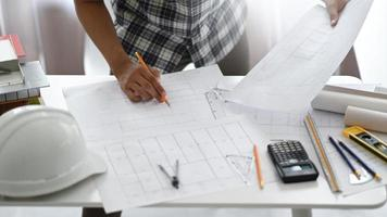 designer homem segurando um lápis, examinando os planos da casa. foto