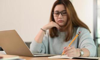 uma adolescente de óculos usa um lápis para escrever em um caderno. foto