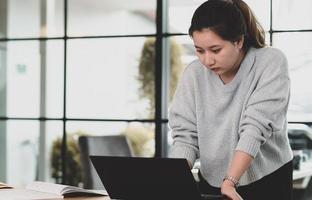 uma adolescente olha para a tela do laptop em cima da mesa. foto