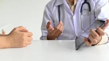 trabalhadores médicos em jalecos de laboratório e estetoscópios usam um tablet. foto