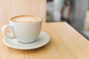 uma xícara de café cappuccino com leite de arte na mesa de madeira foto