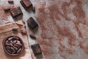 cacau em pó espalhado com pedaços de chocolate e tigela de grãos de cacau foto