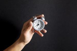 mão segurando um pequeno relógio vintage foto