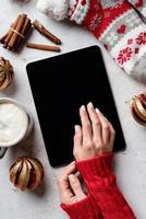 desktop de natal com tablet rodeado de café, meias foto