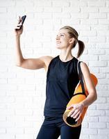 jovem sorridente fitness fazendo selfie após o treino foto