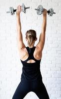 mulher mostrando os músculos das costas e braços treinando com um haltere foto